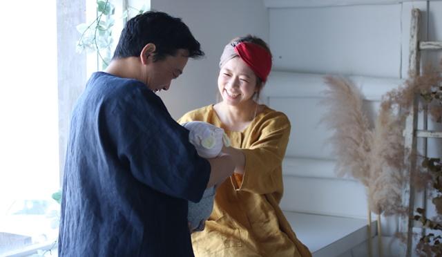 バースクロス着用のご夫婦と赤ちゃん